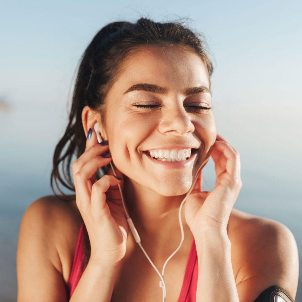 cheerful-sports-woman-listening-music-in-earphones-FJH6PY8.jpg